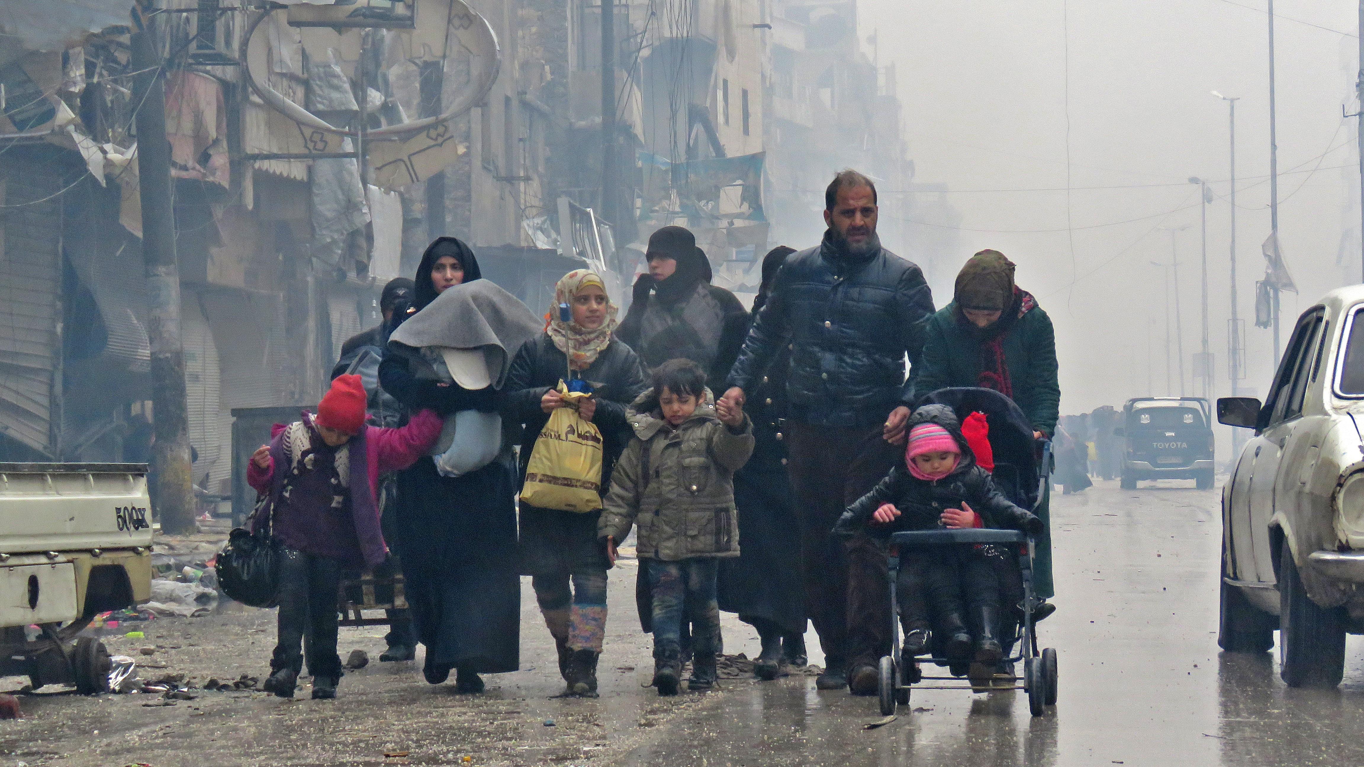 Syrian residents, fleeing violence in the restive Bustan al-Qasr neighbourhood, arrive in Aleppo's Fardos neighbourhood. Image credit: AFP