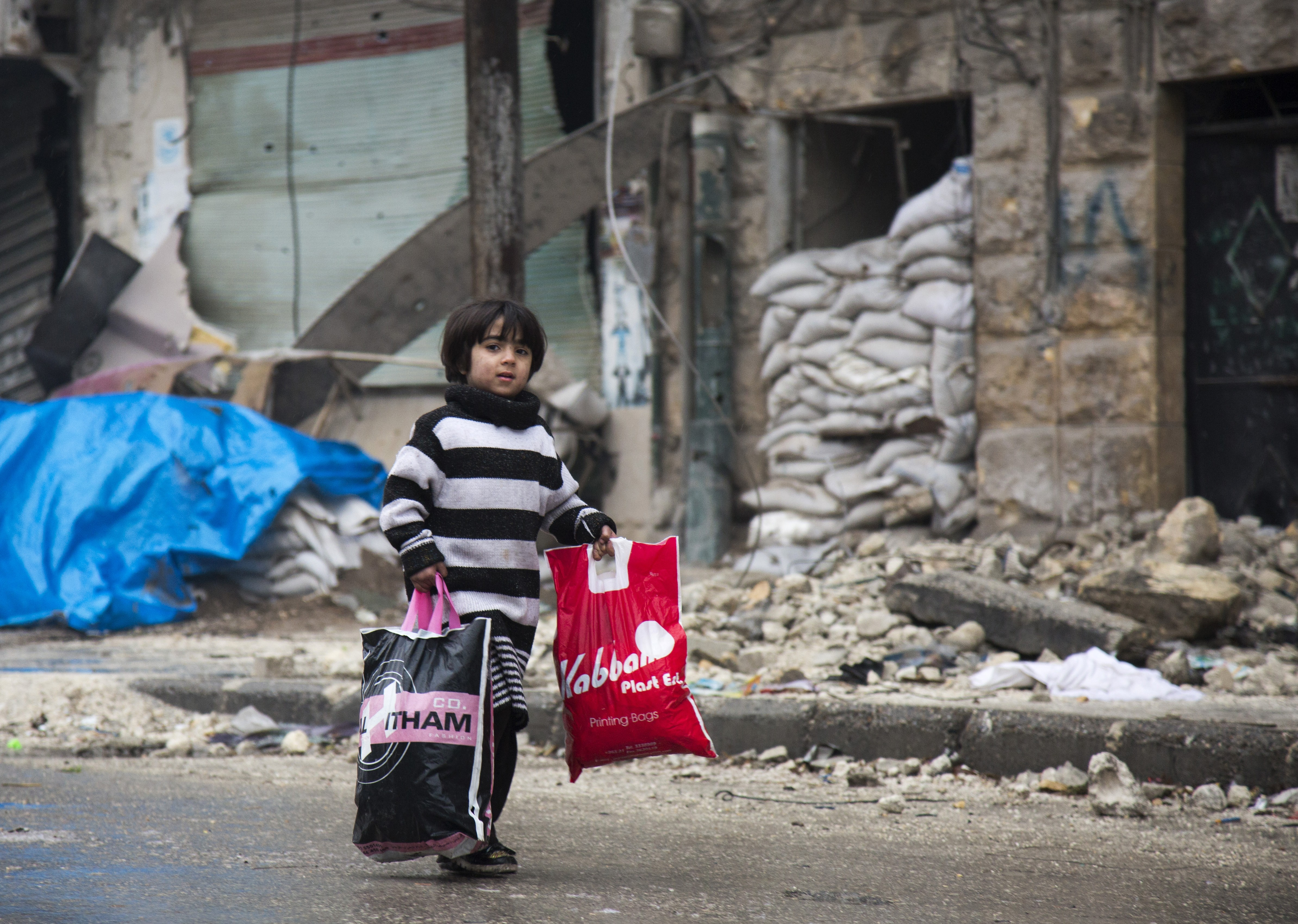 A Syrian boy is seen among other civilains leaving a rebel-held area of Aleppo towards the government-held side on December 13, 2016. Image credit: AFP