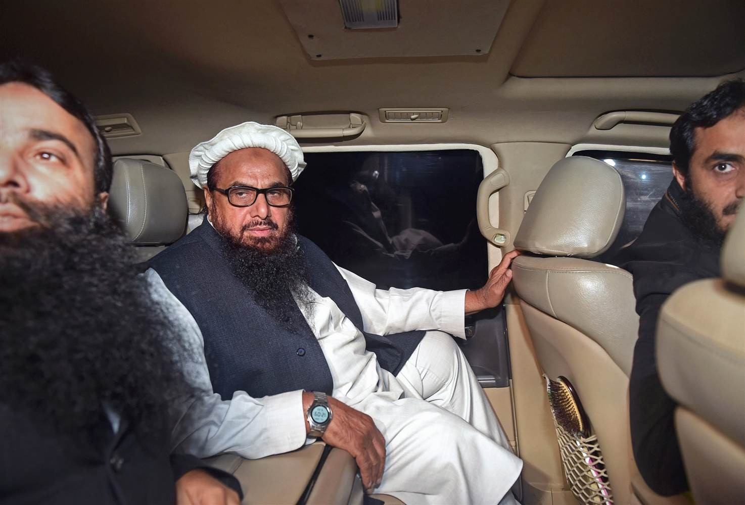 Hafiz Saeed, the Pakistani leader of Jamaat-ud-Dawa, leaves in a car after being detained by police in Lahore, early on Jan. 31, 2017. Image: AFP